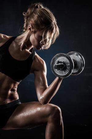 atletisch: Brutal atletische vrouw oppompen muscules met halters Stockfoto