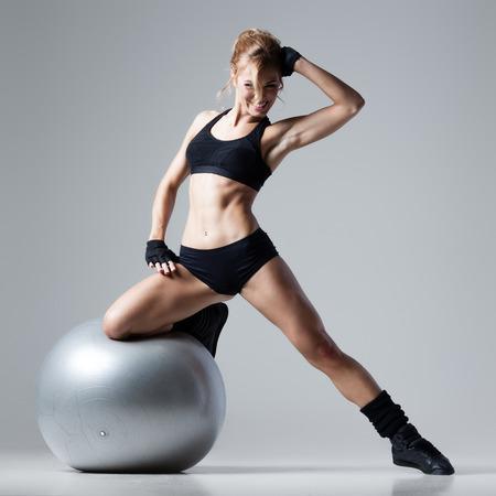 Athletic Frau steht auf einem Gymnastikball auf grauem Hintergrund