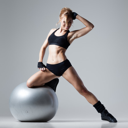 Athletic woman stands on a gym ball on gray background Stock Photo
