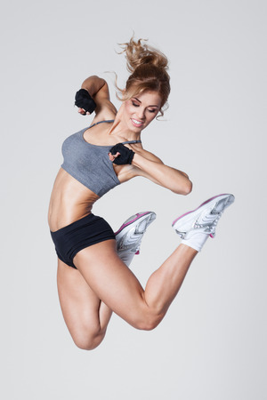 La mujer joven salta al hacer ejercicios aeróbicos sobre fondo gris