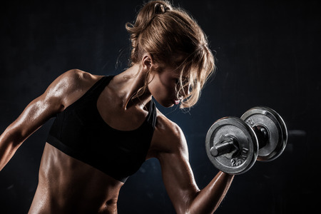 muscle: Brutal athletic woman pumping up muscles with dumbbells Stock Photo