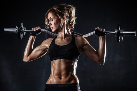 Brutal athletic woman pumping up muscles with barbell photo