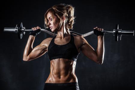 Brutal atletische vrouw oppompen spieren met barbell Stockfoto