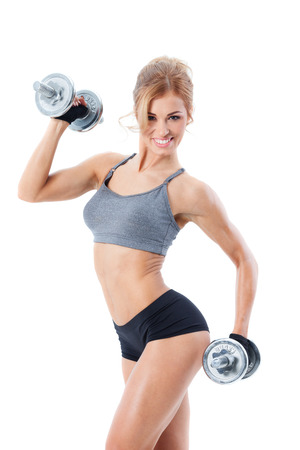 body pump: Smiling athletic woman pumping up muscles with dumbbells on white background
