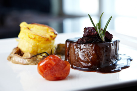 Roasted beef tenderloin with herb-potato muffin, mushroom ragout, baked tomatoes and rosemary-currant sauce Imagens