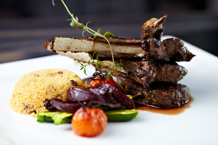 Grilled lamb carre with warm couscous salad, roasted vegetables, Dijon mustard and red wine sauce