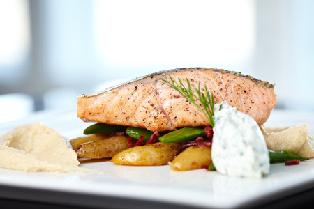 Baked salmon with roasted cauliflower cream, almond potatoes, peas-chorizo ​​salad and cream cheese-herb sauce. photo