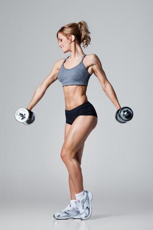 Lachende atletische vrouw oppompen spieren met halters op een grijze achtergrond Stockfoto