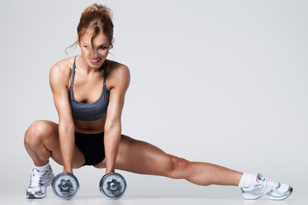 athletic: Smiling athletic woman pumping up muscles with dumbbells and stretching legs Stock Photo