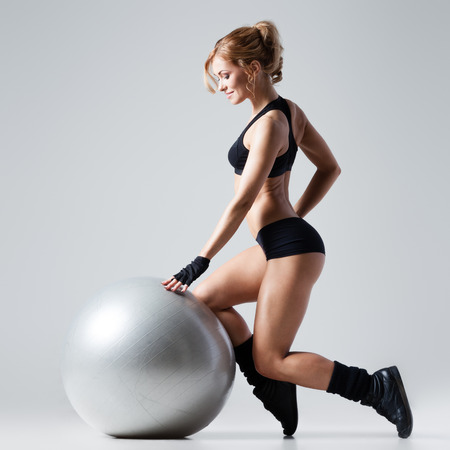 Athletic woman makes exercises on a gym ball on gray background photo