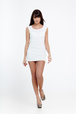 Young beautiful female model in white dress walks on gray  Banque d'images