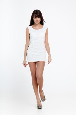 Mooie jonge vrouw model in witte jurk wandelingen op grijs Stockfoto
