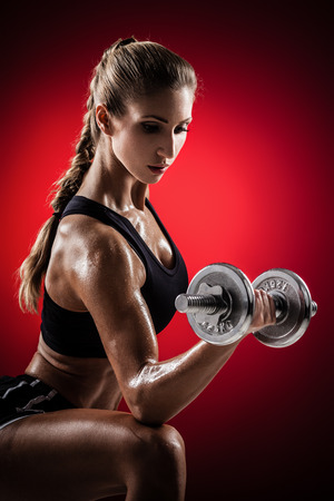 Brutal athletic woman pumping up muscles with dumbbells on red