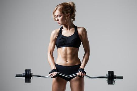 Lächeln athletische Frau Aufpumpen muscules mit Langhantel auf grauem Hintergrund