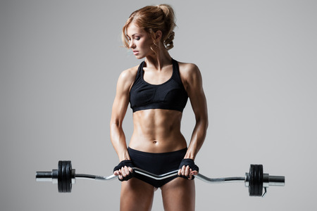 body builder: Smiling athletic woman pumping up muscules with barbell on gray background