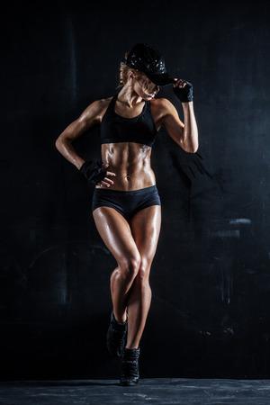 mujeres fitness: Mujer atractiva en una tapa que presenta en la oscuridad Foto de archivo