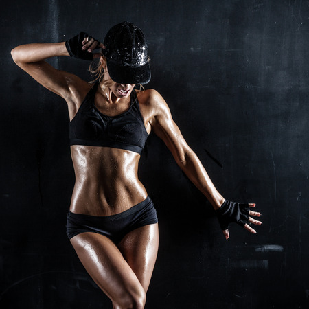 Sexy woman in a cap posing on dark background 写真素材