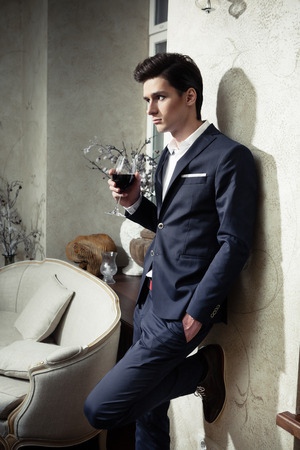 Handsome young man in a classic suit drinking red wine in restaurant