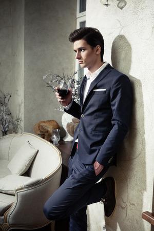 Knappe jonge man in een klassieke pak drinken van rode wijn in restaurant Stockfoto