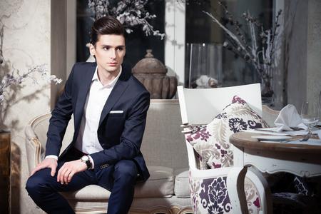 レストランでは、ソファに座っている古典的なスーツでハンサムな若い男