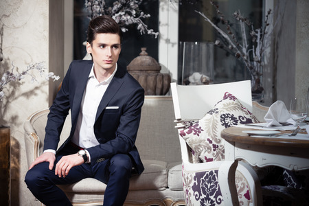 Handsome young man in a classic suit sitting on a sofa in restaurant Imagens