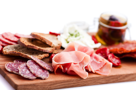 Antipasti and catering platter with different meat and cheese products photo