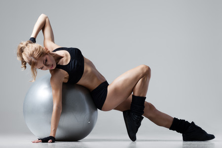 Athletic Frau macht Übungen auf einem Gymnastikball auf grauem Hintergrund