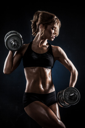 violence in sports: Brutal athletic woman pumping up muscles with dumbbells Stock Photo