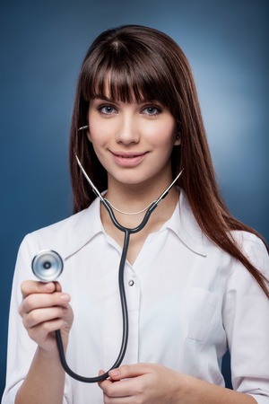 Sexy rse holding stethoscope on blue background Stock Photo