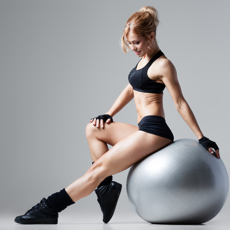 body pump: Athletic woman sitting on a gym ball on gray background