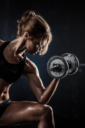 Brutal athletic woman pumping up muscles with dumbbells 스톡 콘텐츠