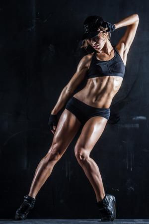 Sexy fit Frau in einer Kappe auf dunklem Hintergrund ausgibt