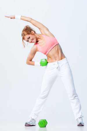 body pump: Smiling athletic woman pumping up muscules with dumbbells on gray background Stock Photo