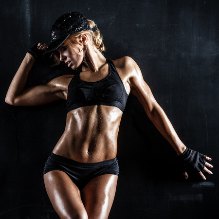 fitness model: Sexy fit woman in a cap posing on dark background Stock Photo