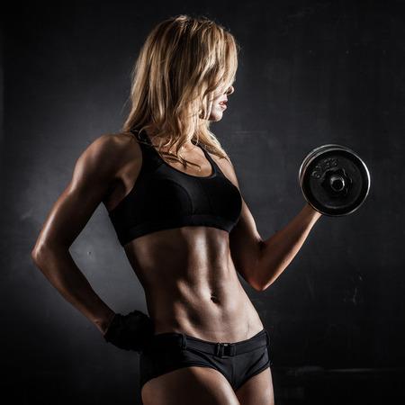 Brutal atletische vrouw oppompen van spieren met halters Stockfoto