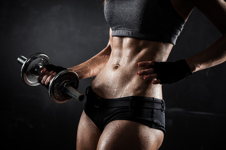athletic: Brutal athletic woman pumping up muscles with dumbbells Stock Photo