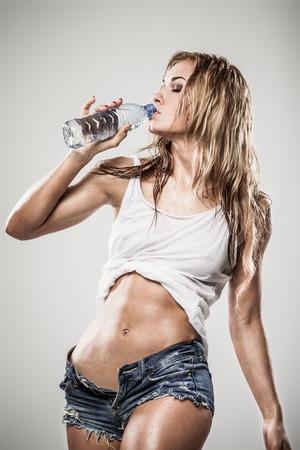 Agua potable deportivo mujer atractiva en ropa mojada en el fondo gris