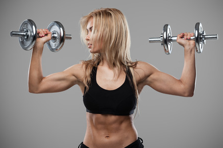 muscle girl: Smiling athletic woman pumping up muscles with dumbbells on gray background