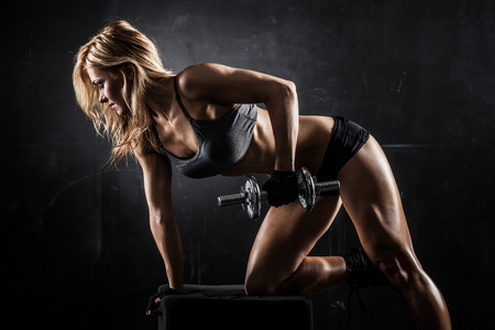 female bodybuilder: Brutal athletic woman pumping up muscles with dumbbells Stock Photo