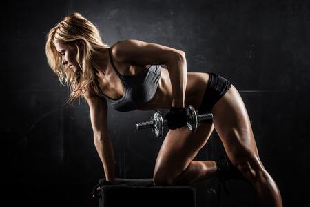 ginástica: Mulher atlética Brutal bombeamento de músculos com halteres