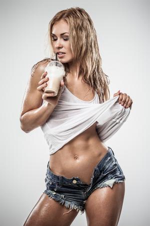 Sexy latte atlético beber caffe mujer en ropa mojada en fondo gris