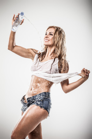 Sexy atletische vrouw drinkwater in natte kleren op een grijze achtergrond