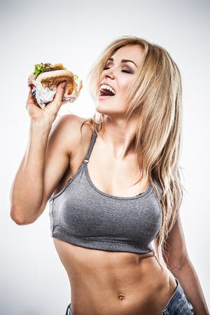 Sexy atletische vrouw eet hamburger op een grijze achtergrond