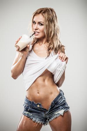 wet clothes: Sexy latte atl�tico beber caffe mujer en ropa mojada en fondo gris