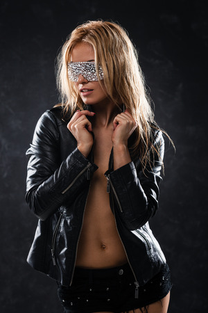 Sexy woman in leather jacket and sunglasses posing on dark background