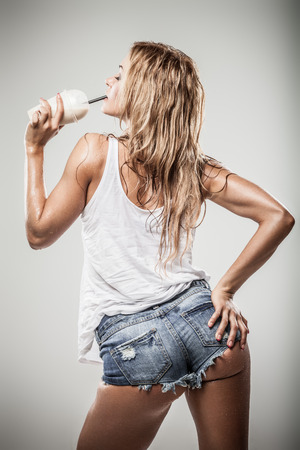 caffee: Sexy athletic woman drinking caffe latte in wet clothes on gray background