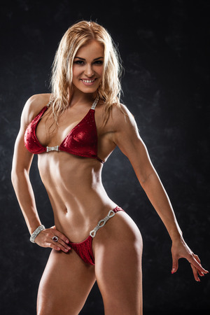 Smiling athletic woman in red bikini showing muscles on dark background Stock Photo