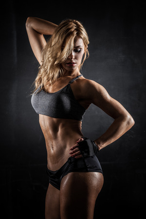 Lächelnde sportliche Frau zeigt Muskeln auf dunklem Hintergrund