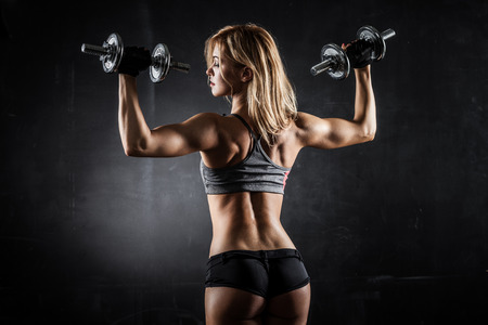 girl fitness: Brutal athletic woman pumping up muscles with dumbbells Stock Photo
