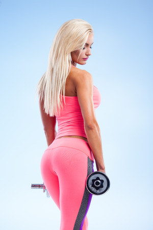 female bodybuilder: Beautiful fitness model posing with dumbbells on blue background Stock Photo